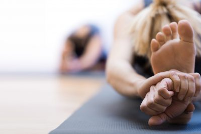 Woman doing physical exercise and stretching legs on a mat, foot close up, healthy lifestyle concept